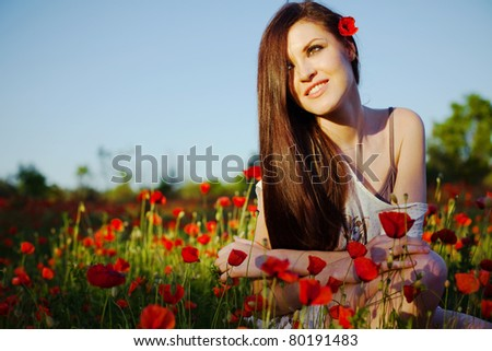portrait of a beautiful girl in a poppy field at sunset