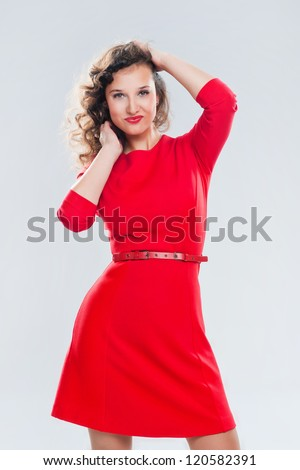 Portrait of a beautiful girl in a red dress on a gray background