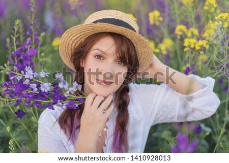 portrait of a beautiful girl in a straw hat and white dress in a flowered field  #1410928013