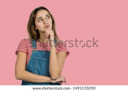 Portrait of a beautiful girl in a striped T-shirt, looks aside with pensive expression, is considering a plan for further action.