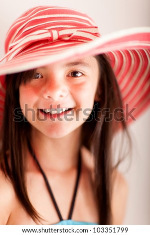 Portrait of a beautiful girl in a summery oufit wearing a hat