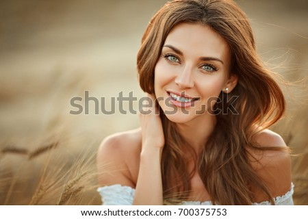 Stock Photo Portrait of a beautiful girl in a white dress in a field with ears at sunset in summer. Close-up