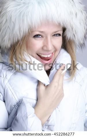 Portrait of a beautiful girl in a white jacket with fur hat #452286277