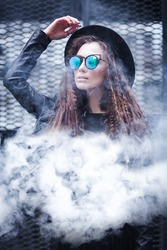 Portrait of a beautiful girl in black hat and sunglasses in a cloud of smoke