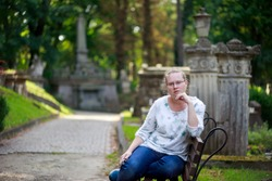 Portrait of a beautiful girl in blue jeans who is sitting on a bench. Lychakiv cemetery. The woman thought. Many graves.