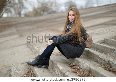 Portrait of a beautiful girl in early spring on the steps. #613980593