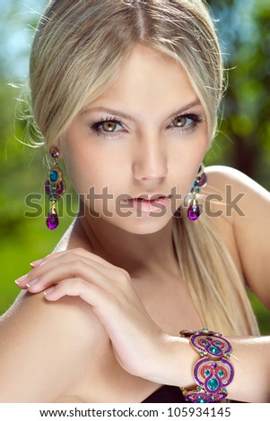 Portrait of a beautiful girl in earrings. Close-up. - stock photo