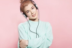 Portrait of a beautiful girl in headphones listens to music and smiles while standing on a pink background in a blue sweatshirt