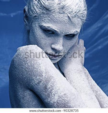 Stock Photo Portrait of a beautiful girl in the frost on his face on a blue ice background