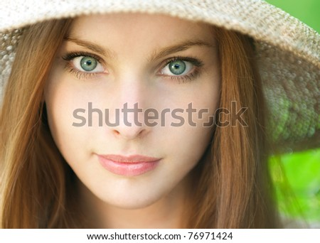 portrait of a beautiful girl in the hat on a green background