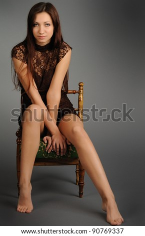 portrait of a beautiful girl on chair on gray background