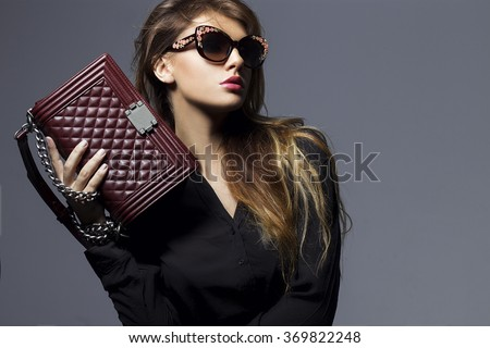 portrait of a beautiful girl posing in studio in black shirt, blue jeans and fashion sunglasses, holding Burgundy handbag . The concept of stylish and sexy women. perfect skin and body