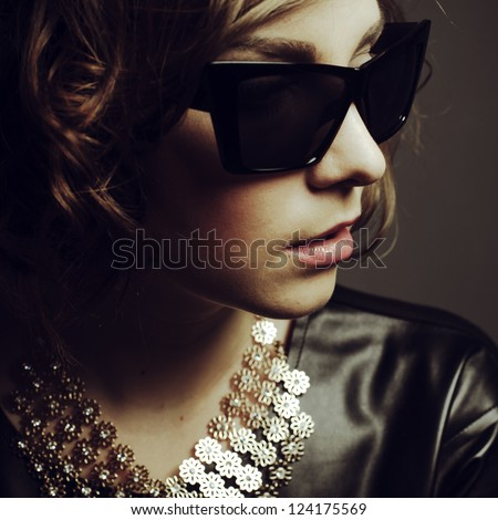portrait of a beautiful girl posing in studio in leather dress and sunglasses