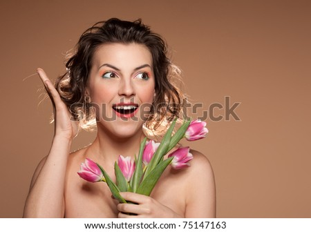 Portrait of a beautiful girl with a bouquet of tulips and wow emotion, closeup.