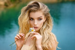 portrait of a beautiful girl with a Daisy in her hands, beautiful make-up