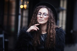 Portrait of a beautiful girl with brown eyes in glasses in a black hat and coat with fur in the cityscape looking in camera. The girl is like Harry Potter