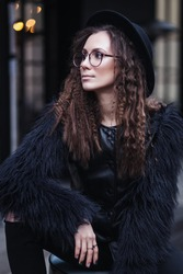 Portrait of a beautiful girl with brown eyes in glasses in a black hat and coat with fur in the cityscape looking away. The girl is like Harry Potter
