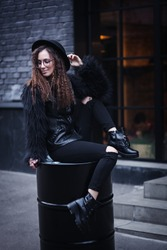 Portrait of a beautiful girl with brown eyes in glasses in a black hat and coat with fur sits on a barrel in the cityscape and looking down. The girl is like Harry Potter