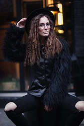 Portrait of a beautiful girl with brown eyes in glasses in a black hat and coat with fur sits on a barrel in the cityscape and looking in camera. The girl is like Harry Potter