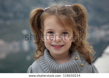 Portrait of a beautiful girl with long curly hair with a warm sweater