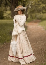 Portrait of a beautiful girl with long hair in a hat, in a long white dress, with a lace umbrella. Stands on a forest path and looks directly into the camera. Historical reconstruction