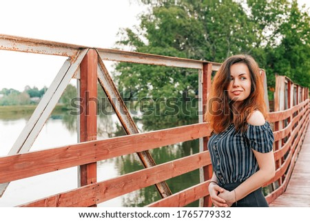 Portrait of a beautiful girl with long hair on a bridge with red wooden beams on the background of summer nature