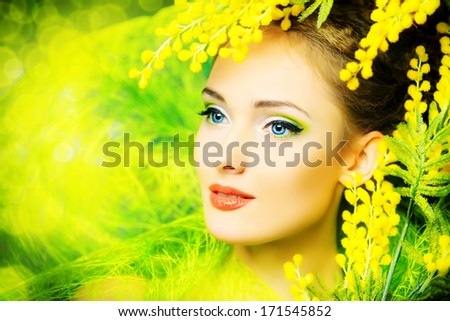Portrait of a beautiful girl with mimosa flowers. Spring.