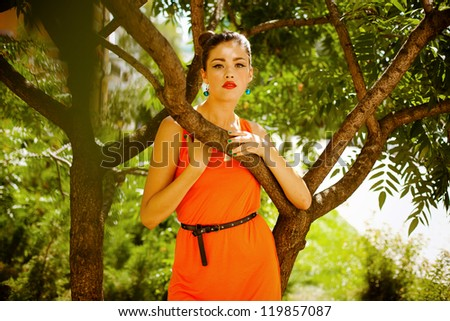 Portrait of a beautiful girl with professional make-up, posing in park near the beautiful tree