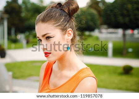 Portrait of a beautiful girl with professional make-up, walking around the city