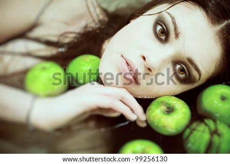 portrait of a beautiful girl with smoky eye makeup, lies in a bath with green apples