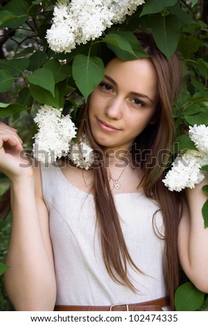 Portrait of a beautiful girl with white lilacs on his head