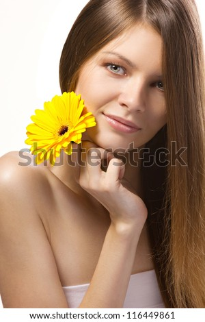 portrait of a beautiful girl with yellow flower on white background - stock photo