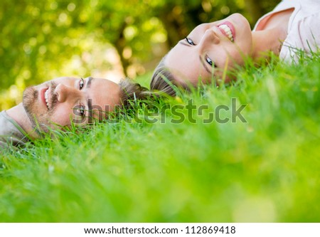 Portrait of a beautiful happy couple lying outdoors