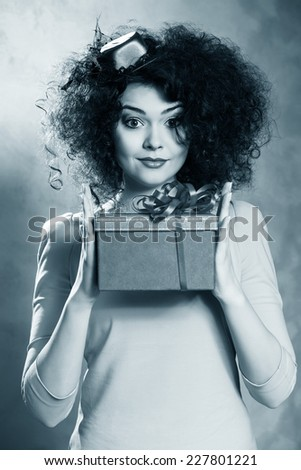 Portrait of a beautiful happy female with red box in hands