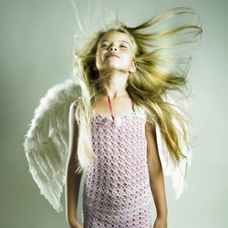 Portrait of a beautiful happy girl with angel wings