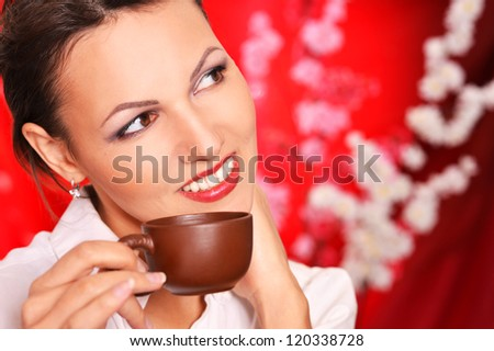 portrait of a beautiful happy woman drinking tea on a red background