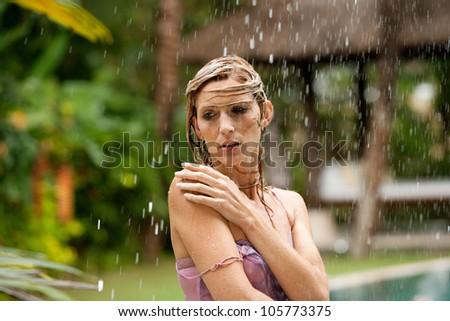 Portrait of a beautiful happy woman enjoying tropical rain falling on her in an exotic garden.