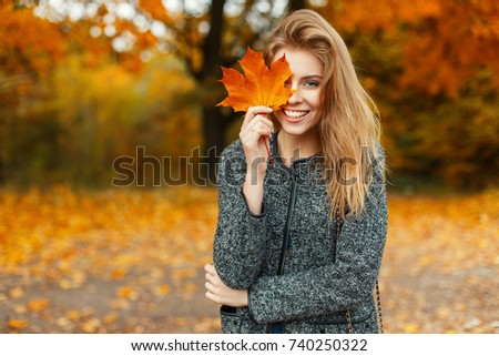 Portrait of a beautiful happy woman with a smile with an autumn yellow leaf in the park #740250322