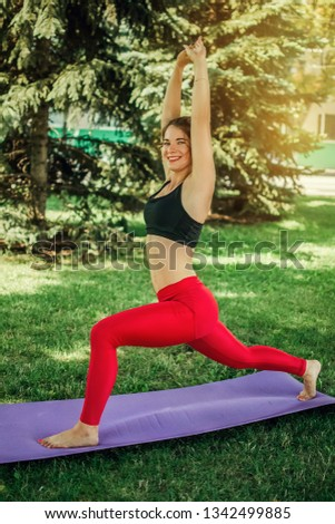 Portrait of a beautiful happy yoga girl in a bright vest keeps a folded purple yoga mat after a practice session in the fresh air, in the background is green nature.  #1342499885