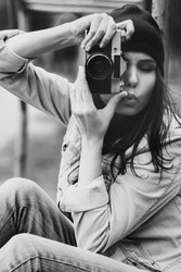 portrait of a beautiful hipster girl in a cap and a denim jacket with a camera taking photos outdoor