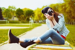 portrait of a beautiful hipster girl with a camera taking photos and sitting on a children's slide in the park
