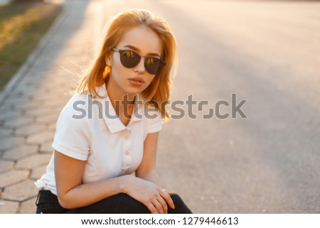 Portrait of a beautiful hipster young woman in stylish sunglasses in a white polo t-shirt in black jeans at sunset. American girl is sitting on an asphalt road. #1279446613