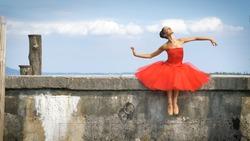 Portrait of a beautiful light ballerina, in a lush red dress, sits on a stone pier, tender. Concept: ballet dancer, slim, diet, light women, flexibility, beautiful figure, healthy lifestyle, sky.