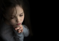 Portrait of a beautiful little baby girl praying. Facial expression. Kid and emotions. Faith and the Bible concept.