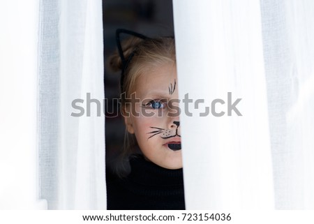 Portrait of a beautiful little emotional blue-eyed girl in the form of a black cat with makeup on her face #723154036