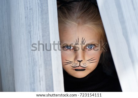 Portrait of a beautiful little emotional blue-eyed girl in the form of a black cat with makeup on her face #723154111