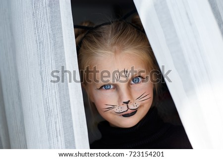 Portrait of a beautiful little emotional blue-eyed girl in the form of a black cat with makeup on her face #723154201
