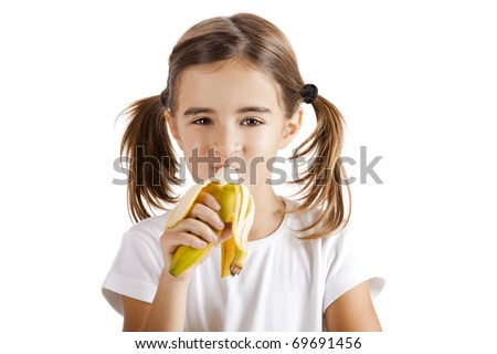 Portrait of a beautiful little girl eating a banana
