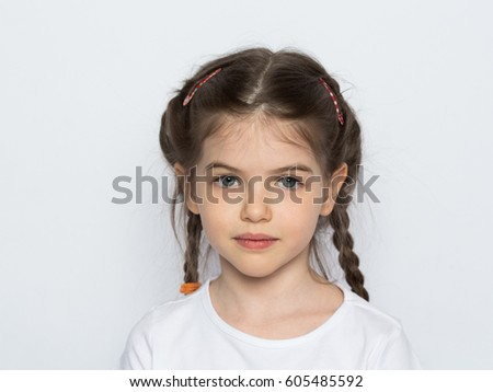 Portrait of a beautiful little girl in a white T-shirt