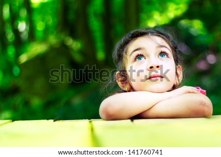 Portrait Of A Beautiful Little Girl In The Forest. With Hands On Chin Looking Up